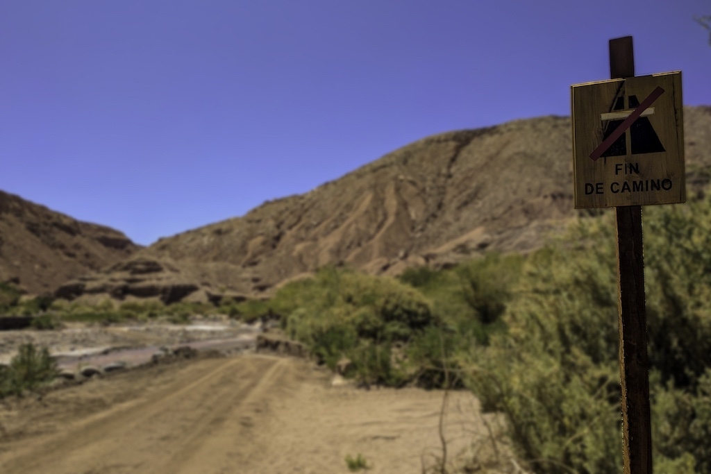"A sign reading ""Fin de Camino"" on an empty desert road"