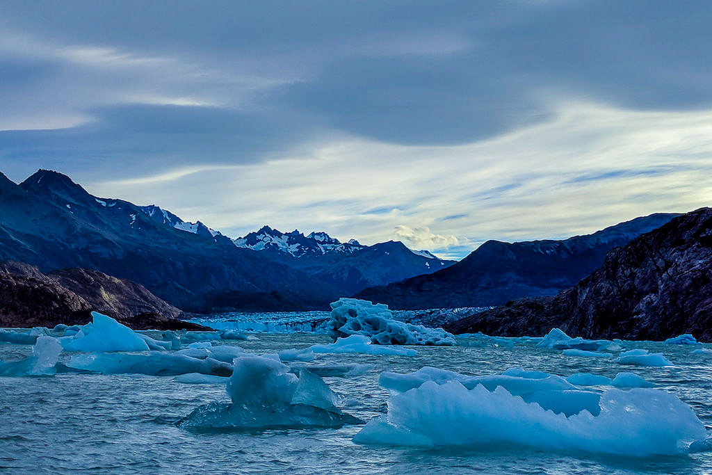 Viedma Bay, full of icebergs, with glowing clouds as the sun sets over the mountains
