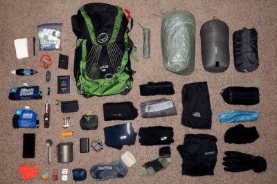 Above view of all necessary trekking gear laid out across a carpet