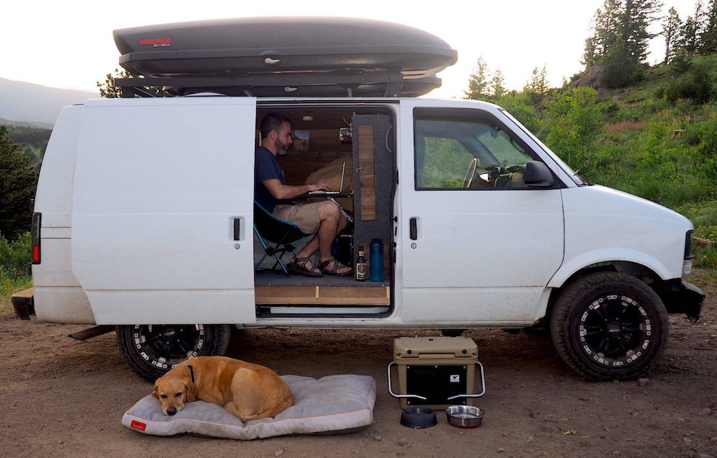 Man typing on a computer in a camper van with a dog laying on a dog bed outside