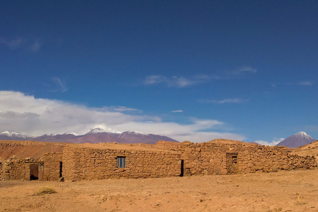 Rebuilt Incan ruins against a backdrop of the Andes Mountains