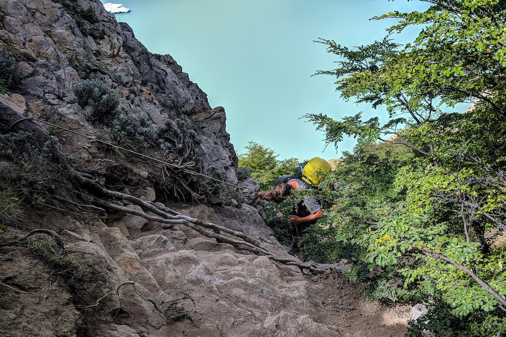 A hiker repelling on a rope down a steep portion of rock with Viedma Bay in the distance