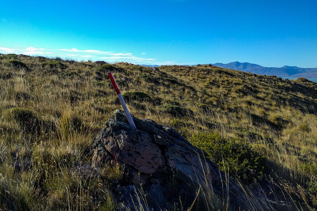 A red trail marker propped up by rocks on the Huemul Circuit Trek outside of El Chalten, Argentina