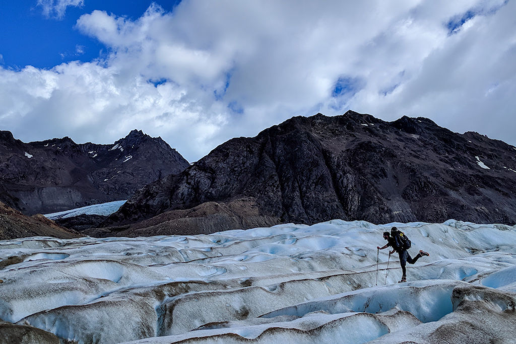 A person treks across Glacier Tunel Inferior wearing crampons while hiking near El Chalten