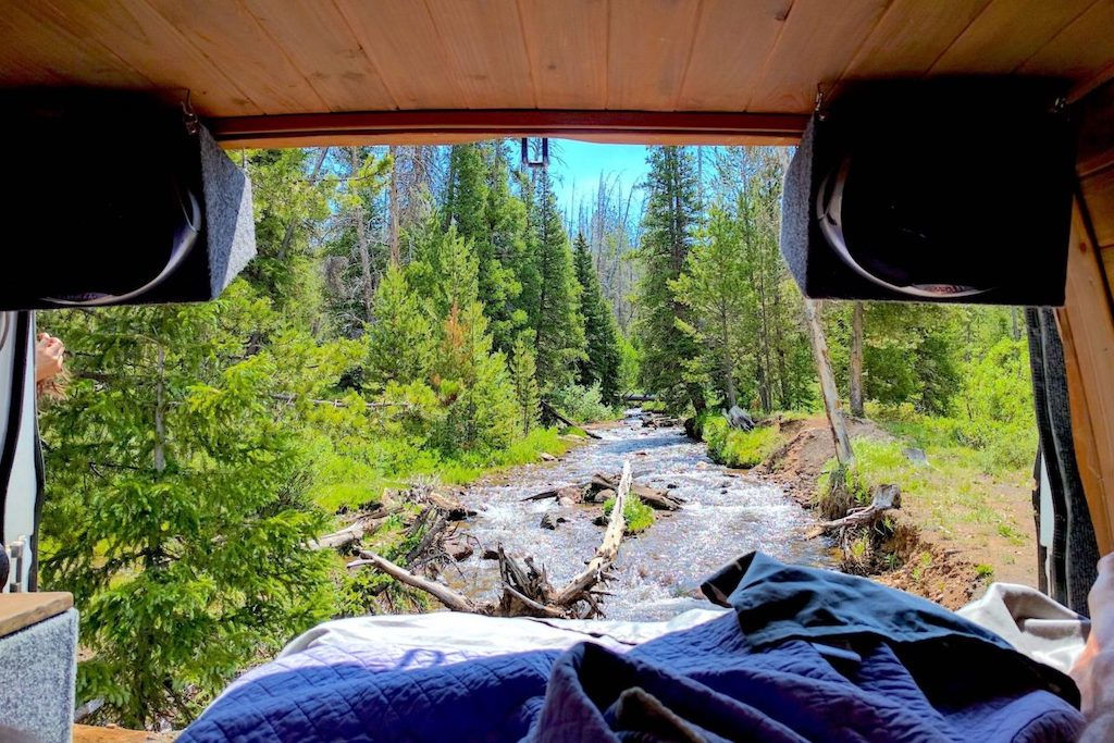 View out the back of a camper van onto a rushing Colorado river
