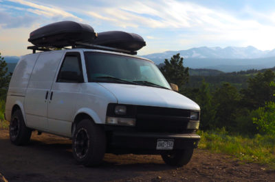 White Chevy Astro Van parked in a camp site in front of a mountain range in Colorado
