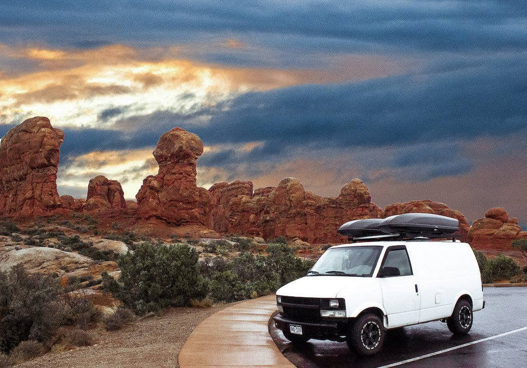 White camper van parked in front of red towers of rock and a sunset in the background