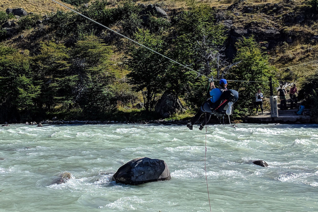 A hiker using the Tyrolean Traverse zipline to cross the Tunel River on the Huemul Circuit trek