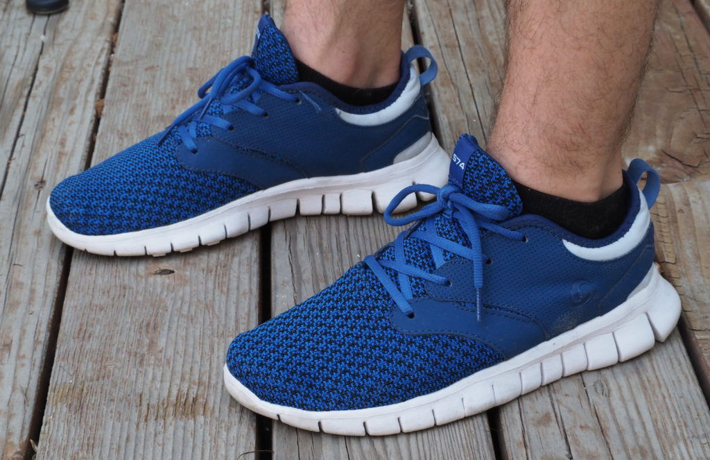 Blue Tesla running shoes on a wood deck