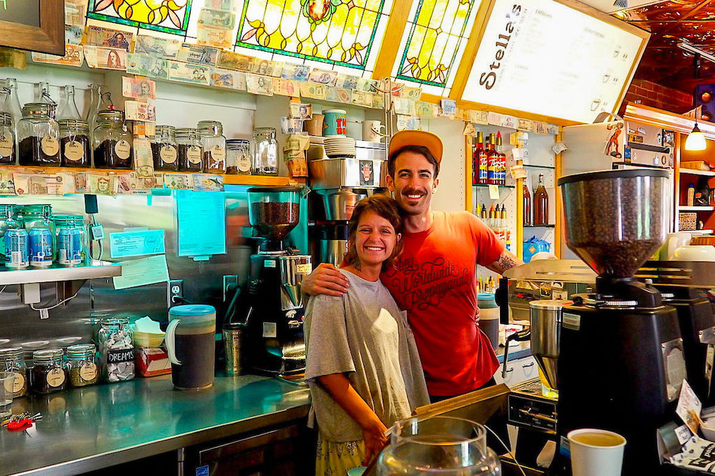 A male and female barista hug as they smile at Stella's Coffee Haus