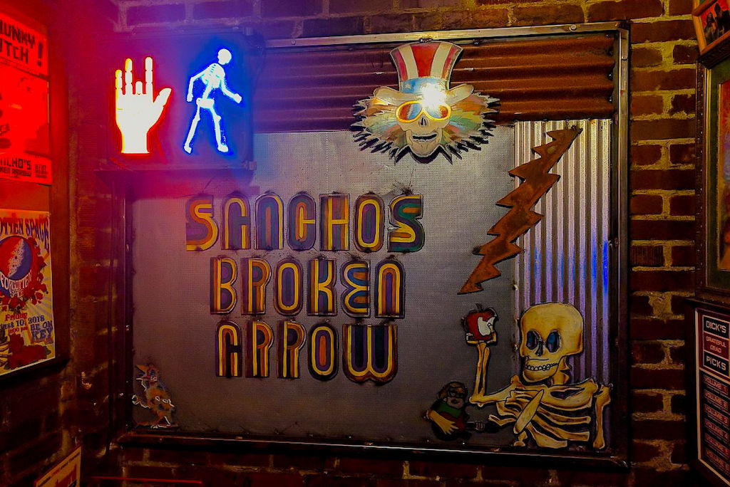 A colorful and psychedelic sign for Sanchos Broken Arrow, an affordable bar in Denver, Colorado