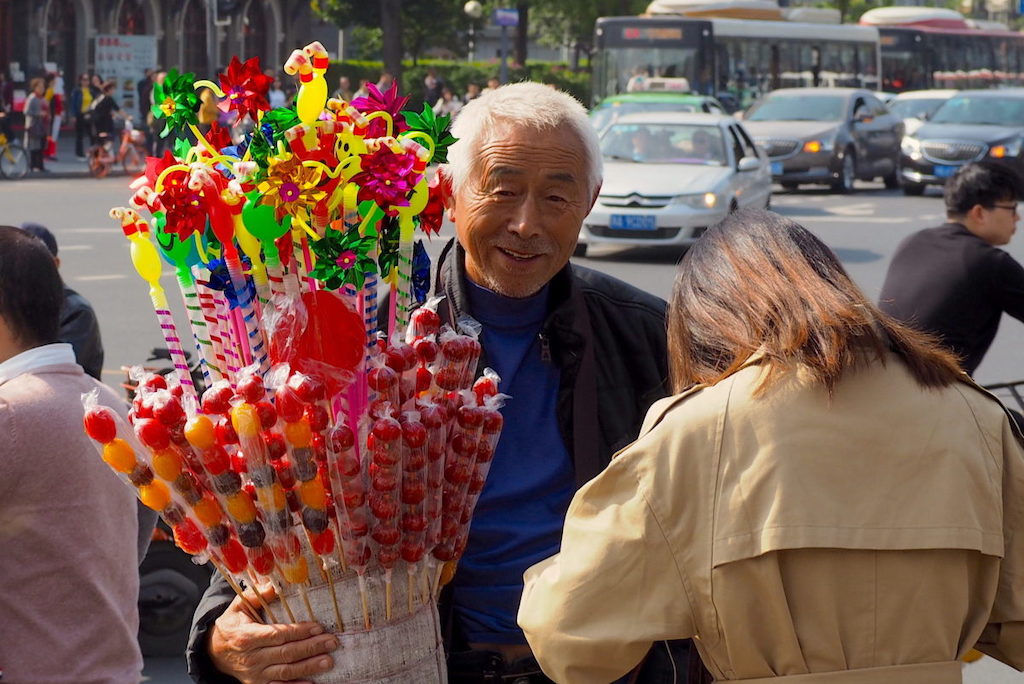A smiling grey-haired Chinese candy vendor on a busy street corner
