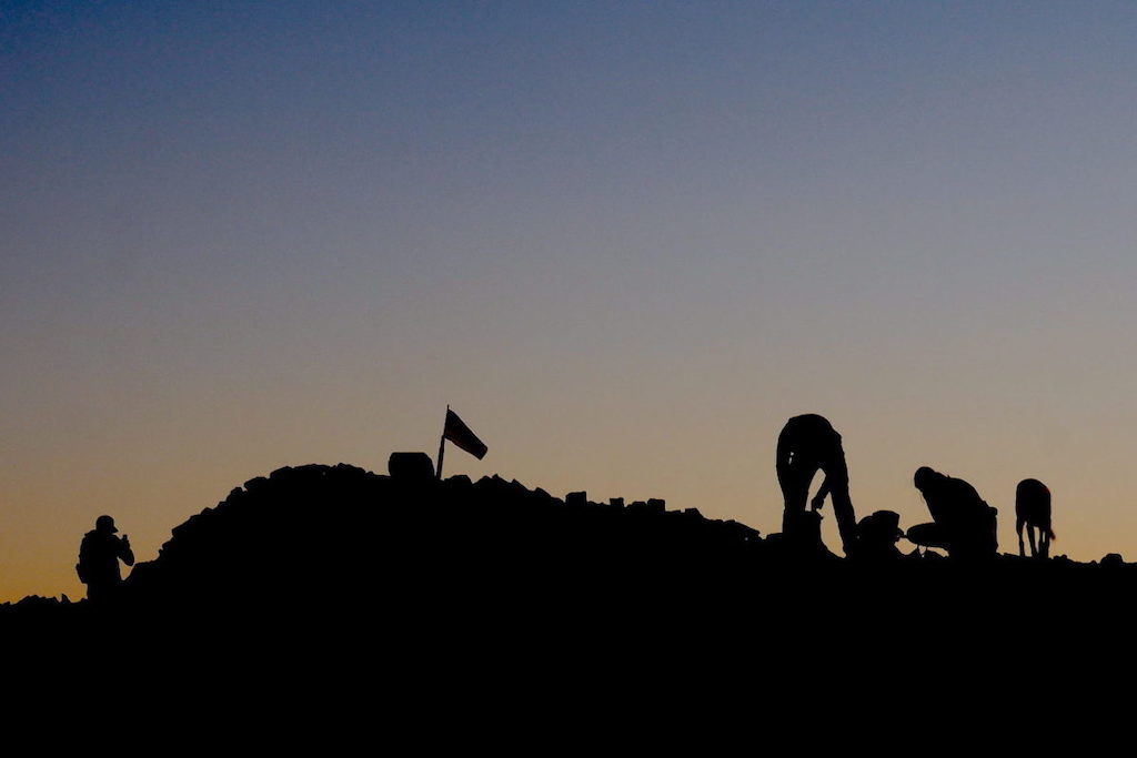 Silhouettes of hikers against a pale sunset atop Mount Lincoln
