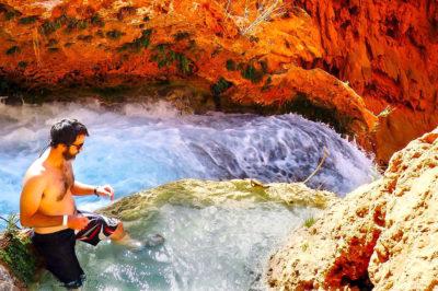 A man sitting in a natural pool of water above Mooney Falls in Havasupai, Arizona