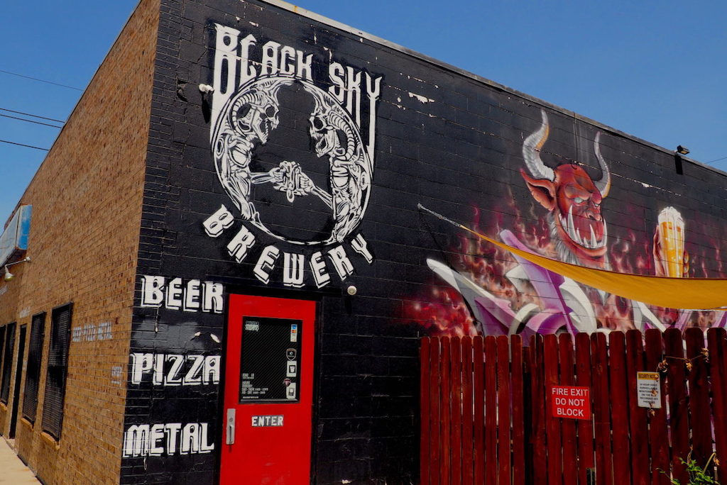 The outside of Black Sky Brewery in Denver, Colorado with a wall painted black and a devil on the logo