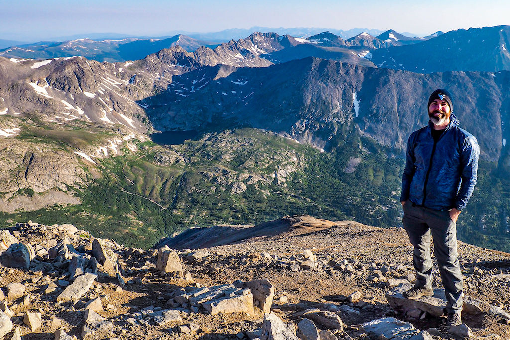 A man standing atop Mount Lincoln wearing Salomon 4D 3 GTX backpacking boots