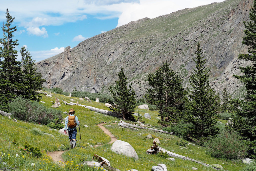 A hiker with a hat on a winding mountain trail