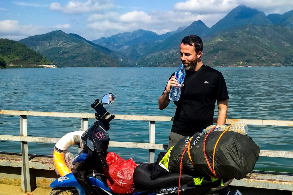 A man drinks from a water bottle on a ferry with a motorbike at his side
