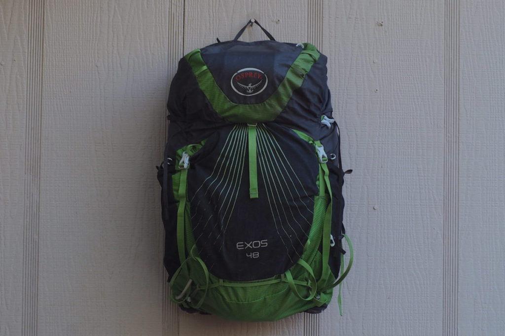Osprey Exos 48 backpack against a green house