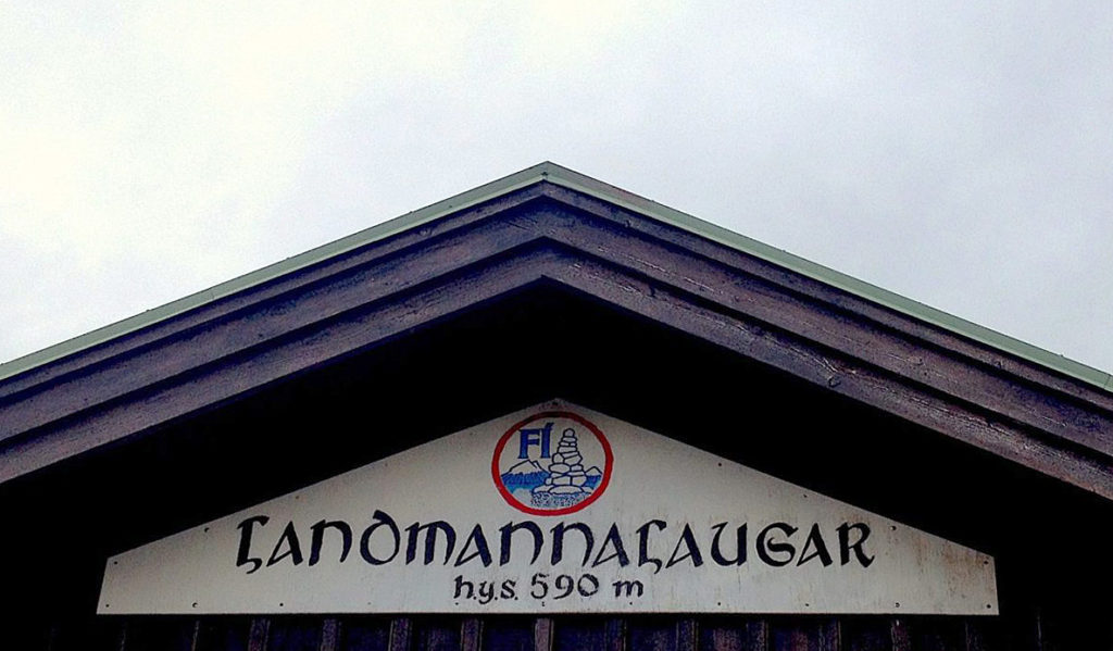 "A sign affixed to a hut reading ""Landmannalaugar - 590m"""