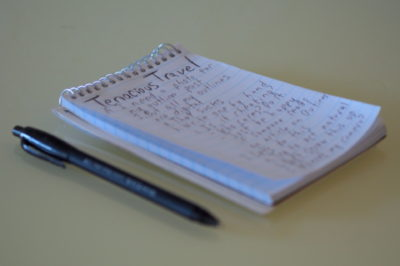 Pad of paper and a pen with a written outline for a travel blog