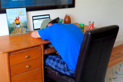 Noel face down on his office desk in front of his laptop working on his travel blog