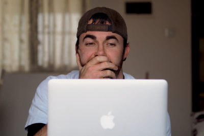 Noel starting tiredly at his computer while typing an article on his travel blog