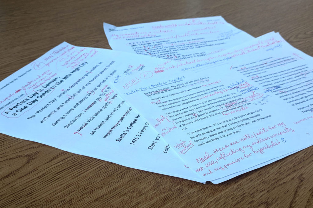 A pile of rough drafts of travel blog articles, edited and marked up with red ink