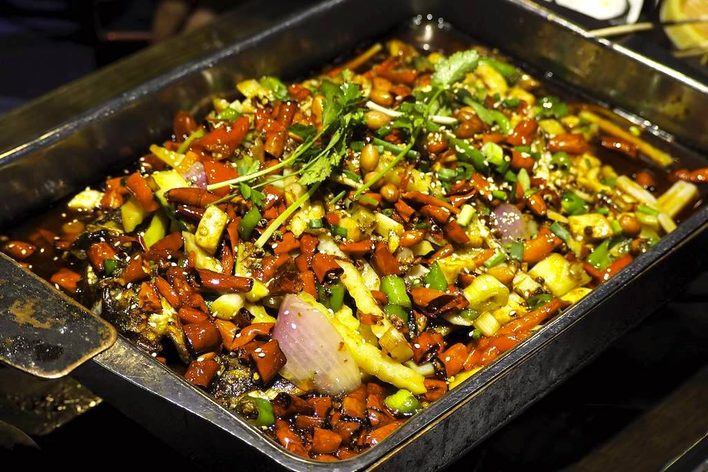 Carp simmering in a chafing dish with onions, peppers, garlic, and more
