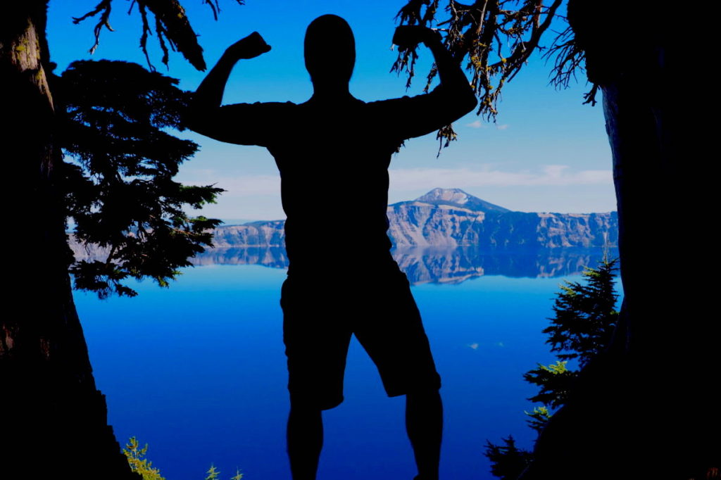 A silhouette flexing in front of Crater Lake, Oregon