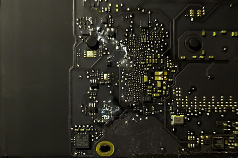 Close up of corrosion and water damage on the logic board of a Macbook Pro