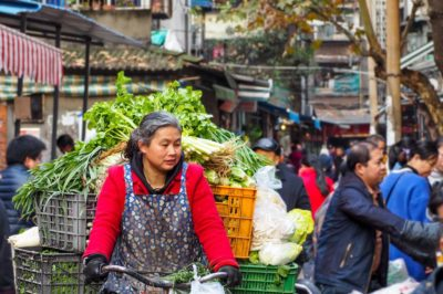 Woman riding a cart full of vegetables down a crowded outdoor market in Chengdu, China