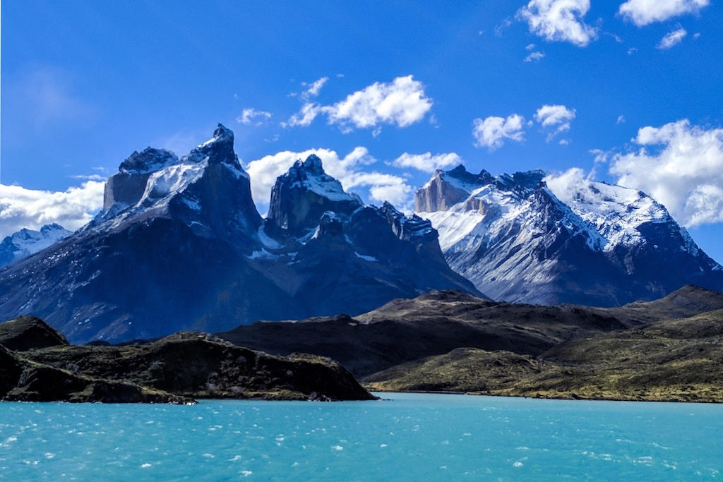 Glacial green Lake Pehoé with a blue sky and Torres del Paine in the distance