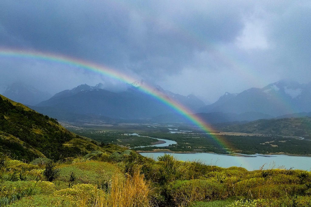 Double rainbow over the hiking trail reaching through a break in the clouds