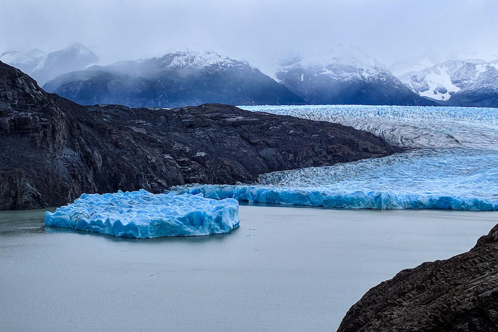 A large iceberg floating in Lake Grey with Glacier Grey and a cloudy mountain range in the distance