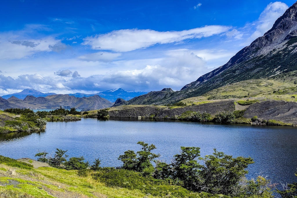 Lake Nordenskjöld backed by blue skies and mountains in the far distance on the 'O' Circuit hike in Torres del Paine