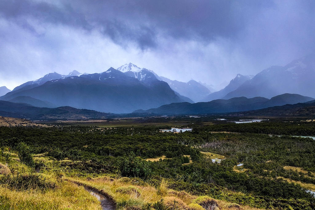 Dark rain clouds above a backdrop of mountains