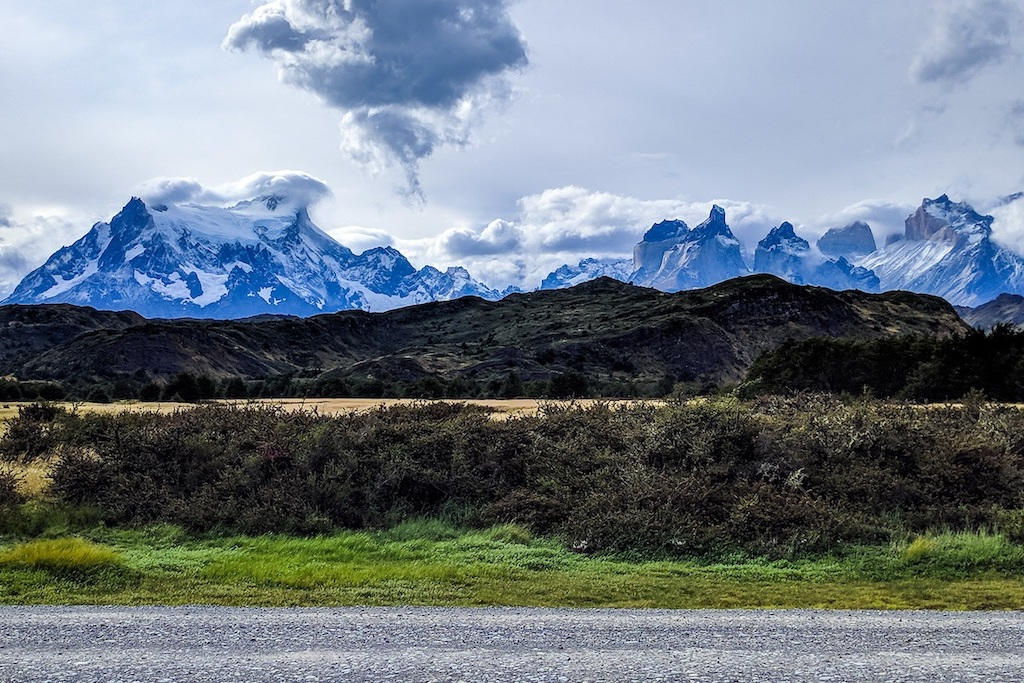A section of road with Torres del Paine looming far in the distance