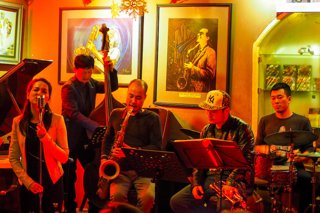 Five jazz musicians passionately play music in Hanoi's warmly lit Binh Minh Jazz Club bar