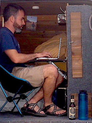 Man sitting and typing on a computer from inside a camper van