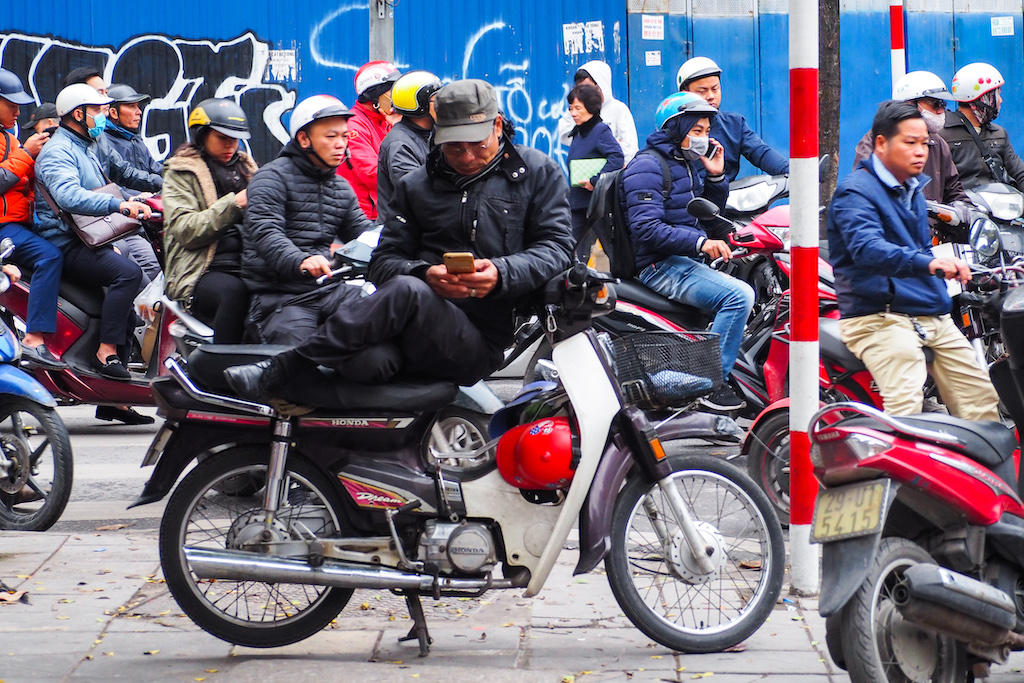 One man sits on his motorbike during a busy day in the streets of Hanoi