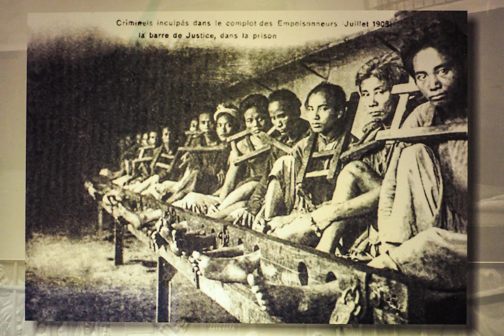 Prisoners sit shackled in wooden restraints, stare at the camera in the Hoa Lo Prison Memorial