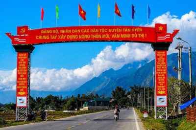 Red arch with Vietnamese text over an open road with mountains and blue skies in the background