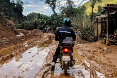 A man sitting on a motorbike in the middle of a muddy dirt road with a wooden shack to his right and jungle in the background