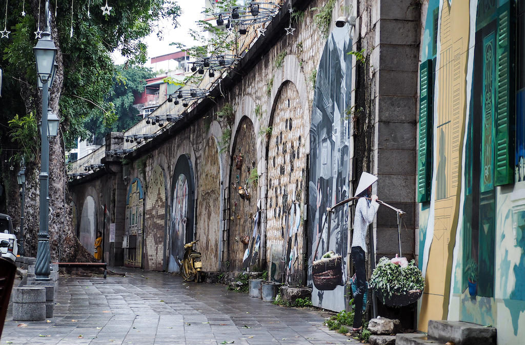 Walls full of street art murals curve with the sidewalk