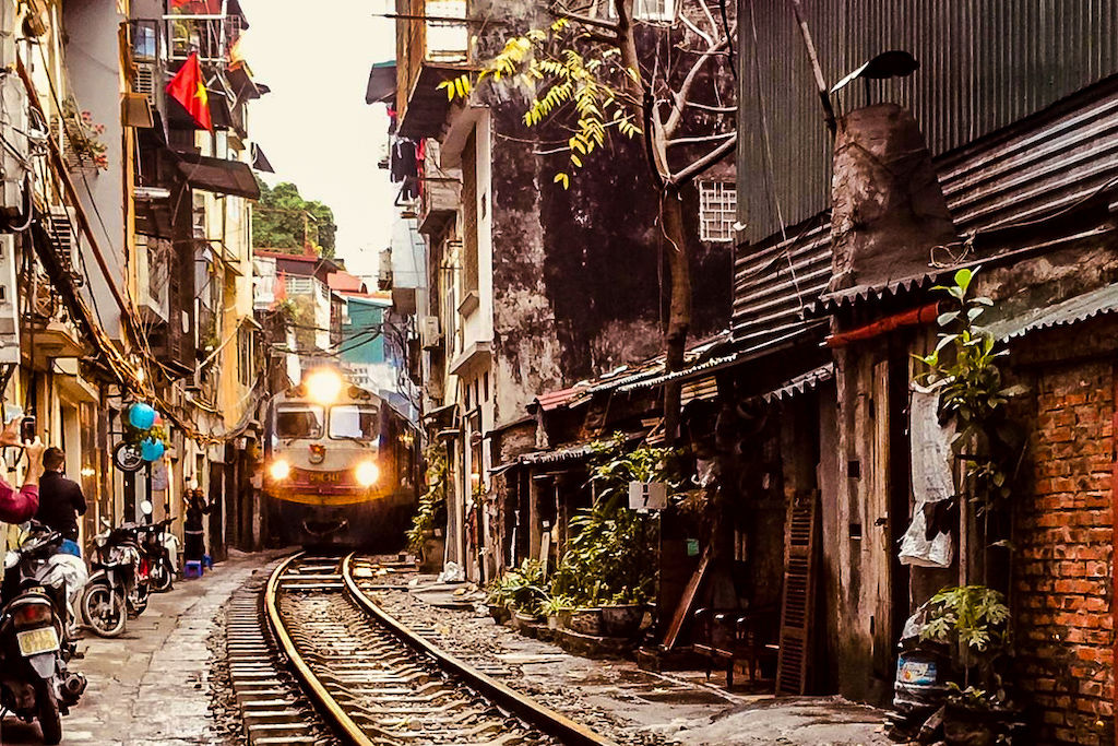 A train squeezes through a narrow Hanoi alley as it moves into the frame