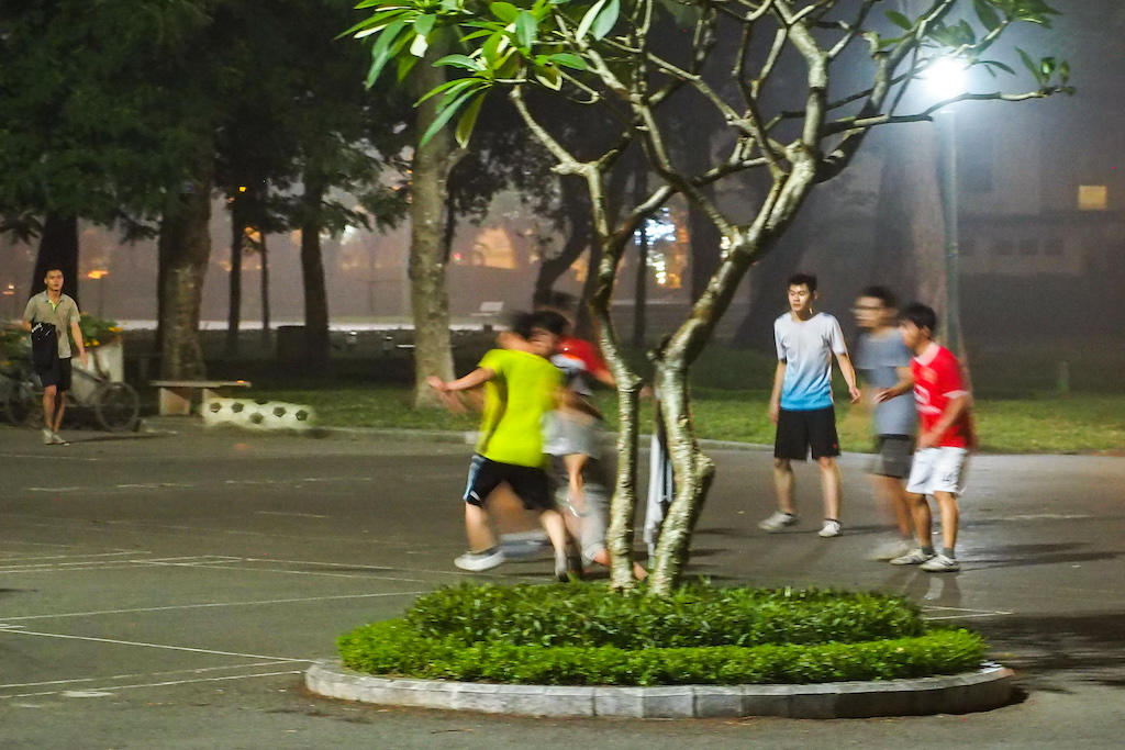 A group of teenagers play soccer on an asphalt pavement at night