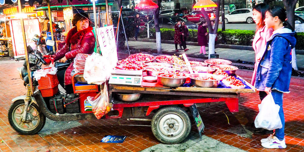 A woman driving a red cart full of baskets of stawberries