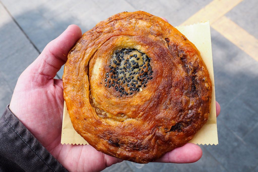 Circular fried pastry filled with meat from a street food cart in Chengdu, China.