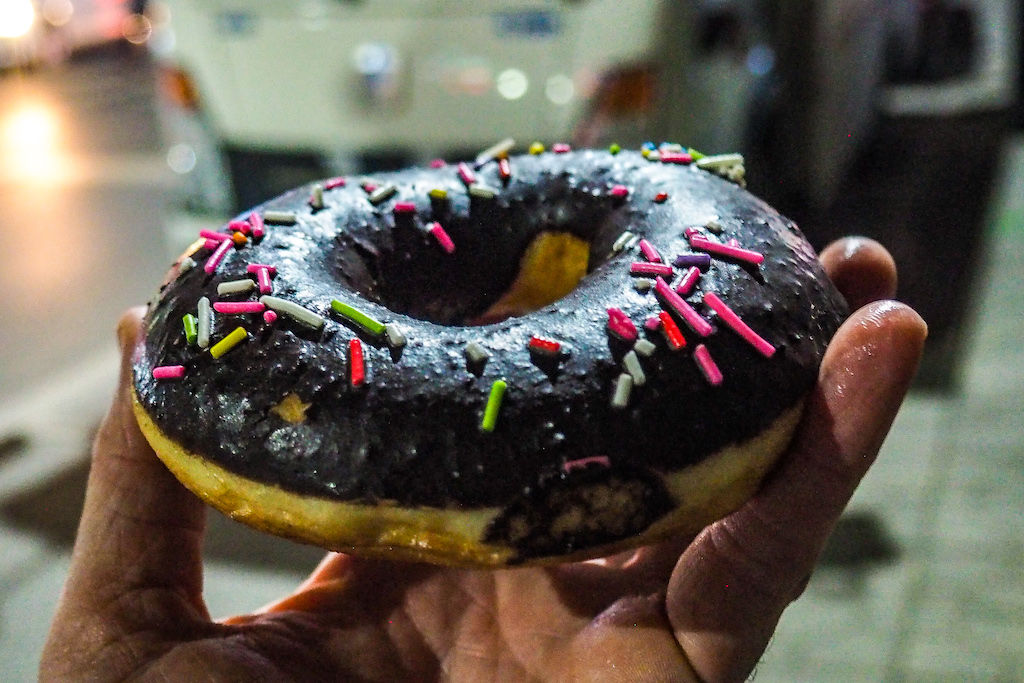 A hand holding up a chocolate donut with sprinkles